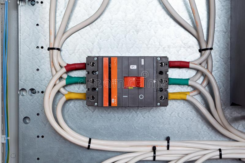 One large power circuit breaker in the electrical Cabinet. Many cables or wires are connected to the switch. Big bunch of wires. Distribution of electricity in stock images