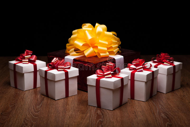 One large red gift box with small gift boxes. One large red gift box with yellow bow with small gift boxes on black background royalty free stock photography