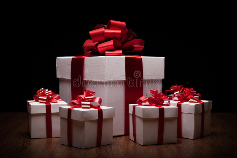 One large white gift box with small gift boxes. On black background stock images