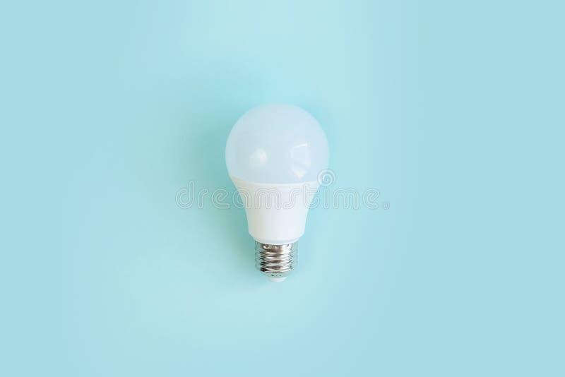 one LED light bulb on blue background. energy saving concept. minimalism stock images