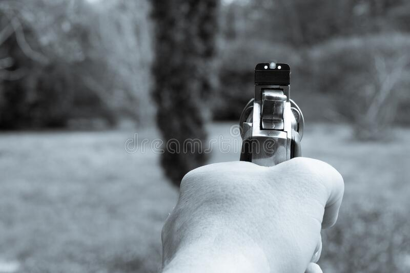 One left hand holds a big silver revolver in the air. A left hand holds a big silver revolver in the air royalty free stock images