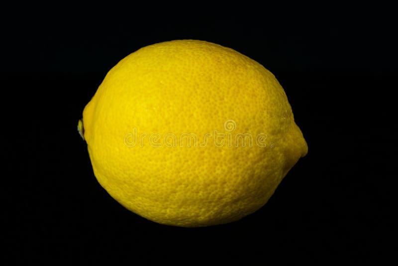 One lemon isolated on black background. royalty free stock photos