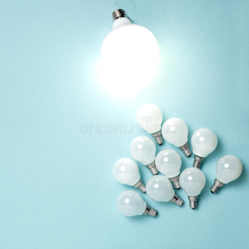 One light bulb outstanding, glowing different. Business creativity idea concepts. Flat lay design royalty free stock photo
