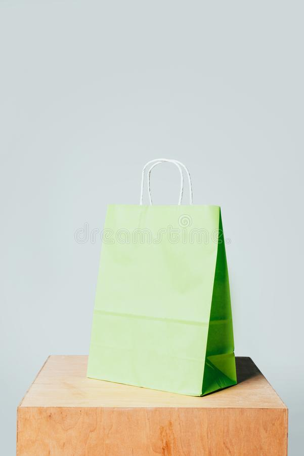 One light green paper bag on wooden stand. Isolated on white, summer sale concept royalty free stock photos