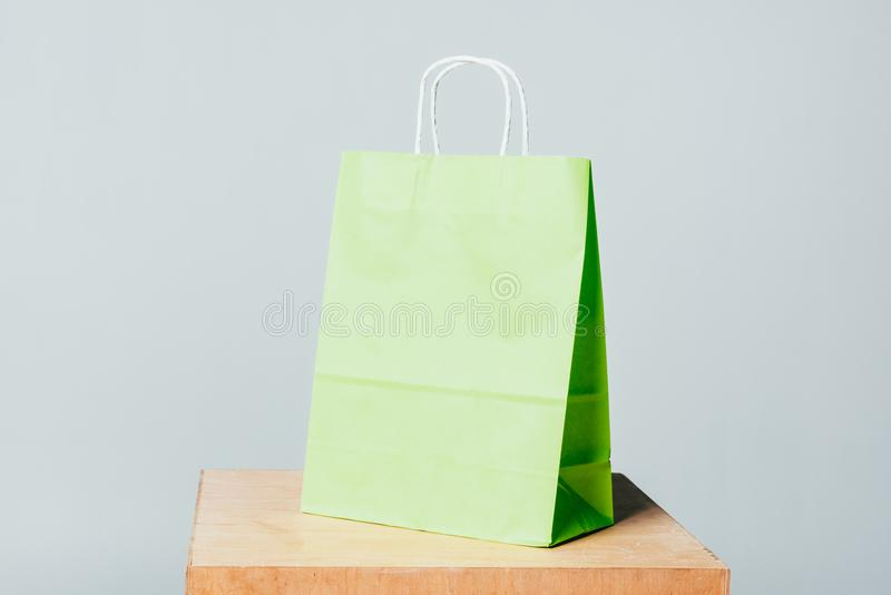 One light green shopping bag on wooden stand. Isolated on white, summer sale concept royalty free stock photography