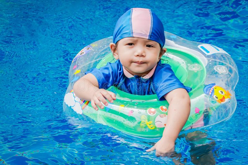 One little girls swimming in the pool with rubber ring, having f royalty free stock photo