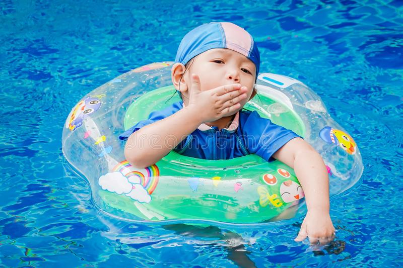 One little girls swimming in the pool with rubber ring. royalty free stock photo