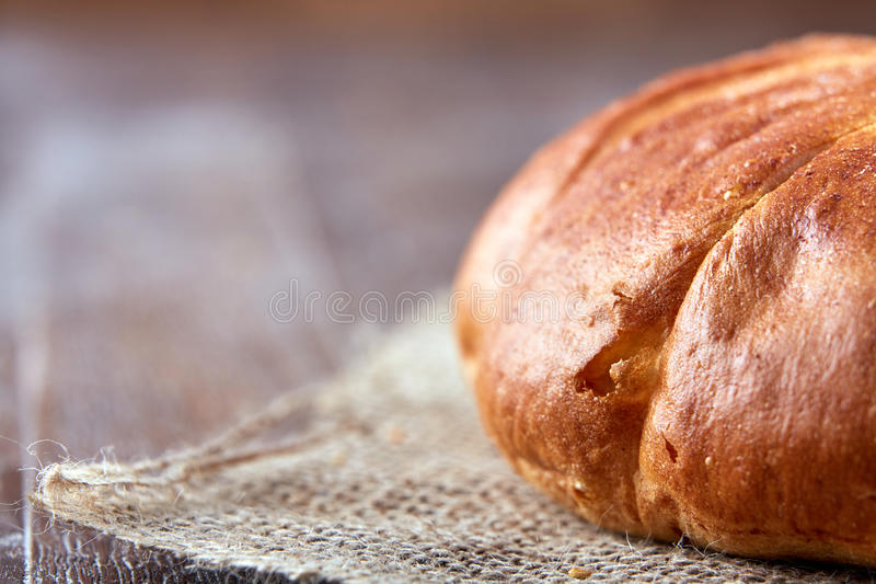 One loaf of bread close-up on a brown background. close-up with blur and macro. stock photo
