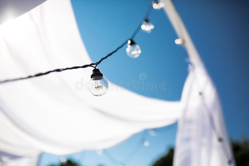 One long electric garland for lighting with white light bulbs against the background of a blue clear sky. Bokeh..Decorative royalty free stock image