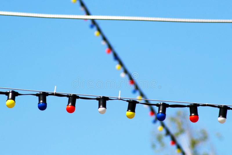 One long electric garland for lighting with white light bulbs against the background of a blue clear sky stock photo