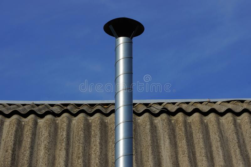 Long metal pipe on a gray slate roof against a blue sky stock photo