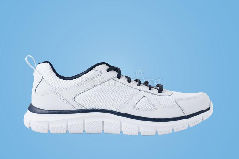 One male white sneakers on a blue background. Sport shoe close up stock photography