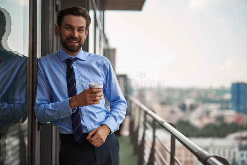One male worker drinking coffee on office balcony stock photos