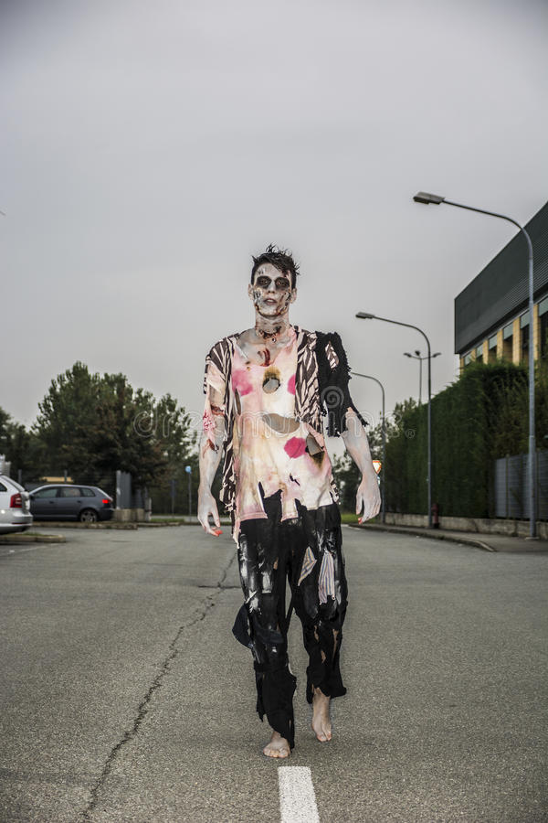 One male zombie standing in empty city street on Halloween stock photo