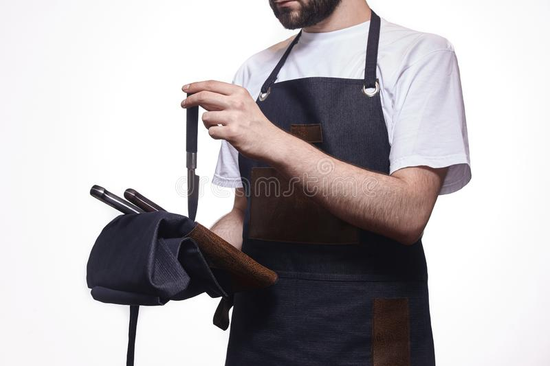 One man, chief uniform, unrecognizable person, holding set of knives stock photos