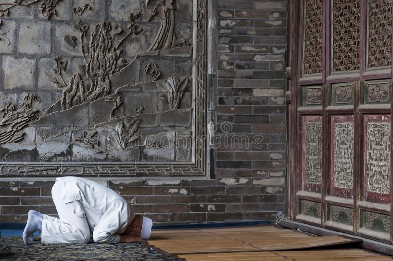 One man praying at the Xian Great Mosque in the city of Xian in China, Asia. royalty free stock images