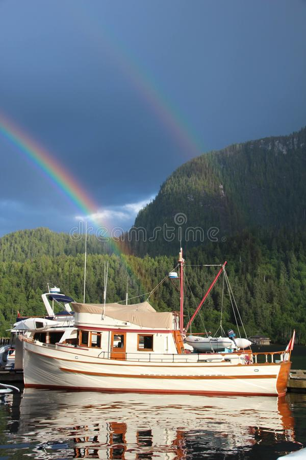 One mans treasure. Rainbow over a boat in the ocean falls marina royalty free stock photo