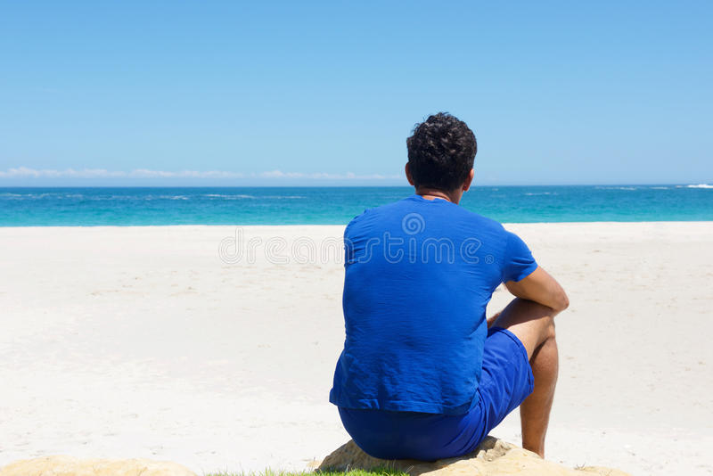 One man sitting alone at the beach. Portrait from back of one man sitting alone at the beach stock image