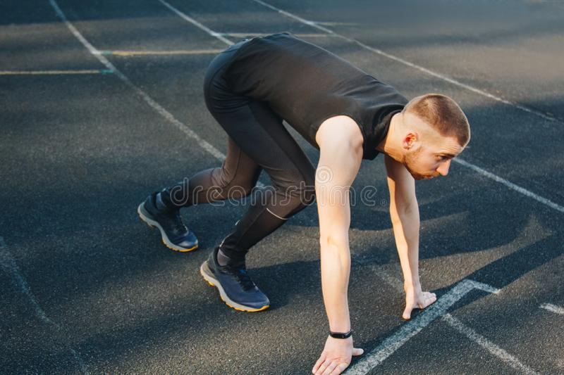One man on the start line awaits the start of the sprint. stadium, rubber track. athletics competitions. Track and field runner in stock photos