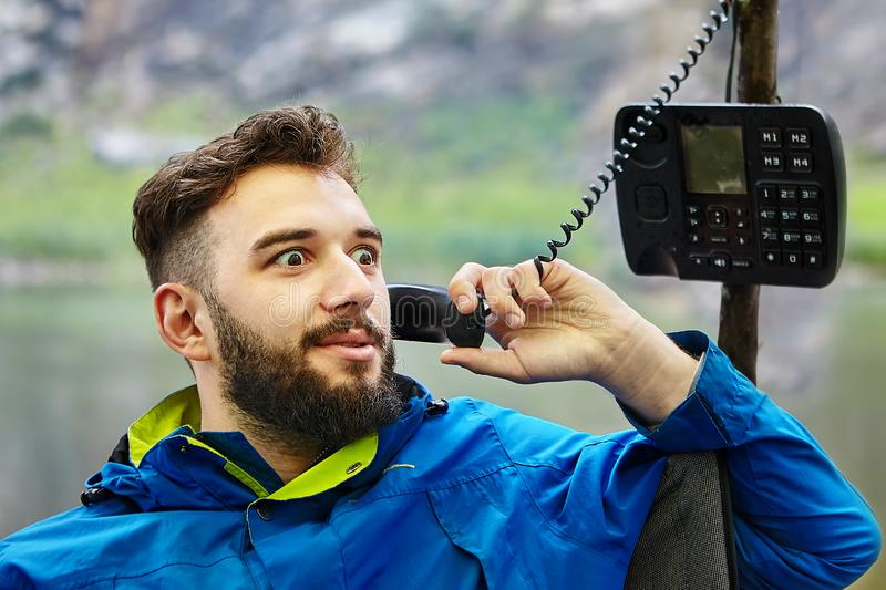 One man uses a wired push-button telephone royalty free stock image