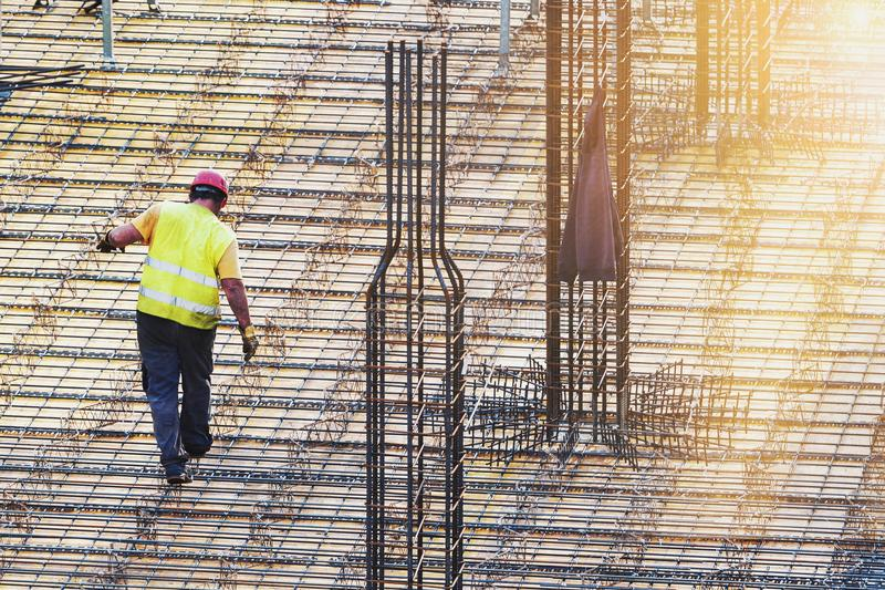 Worker doing metal work at construction site. One man worker doing metal work at construction site with early morning sun rays stock images