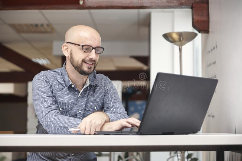 One man, 30-39 years old, using laptop, in modern office interior. stock photos
