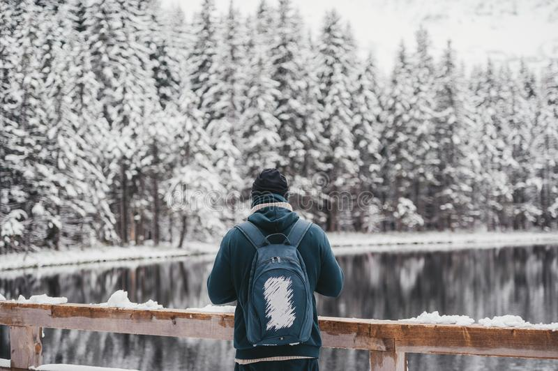 One man young male hiker stands in front of a winter lake looking to the snowy landscape, rear view stock image