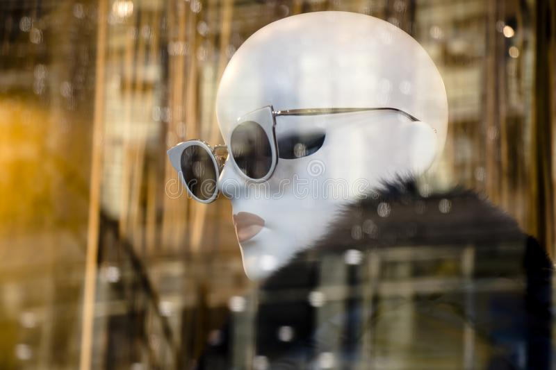 One mannequin doll with sun glasses displayed n the shop window of Max Mara clothing expensive and elegant brand with city lights royalty free stock photography