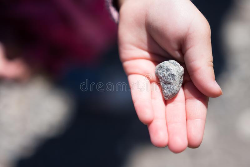 One mans trash is another mans treasure, finders keepers. Small child showing off discovered rock in palm of hand royalty free stock photography