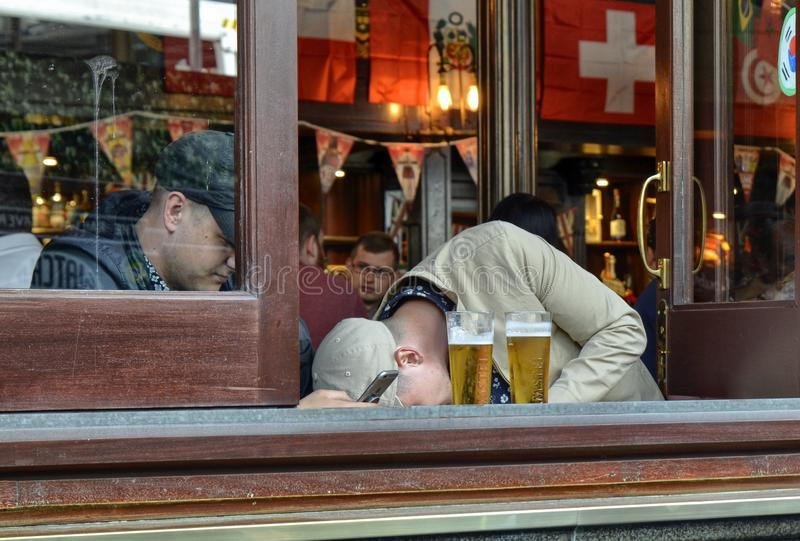 One of the many pubs in central London. London, United Kingdom, June 14 2018. One of the many pubs in central London: friends meet to drink beer and eat royalty free stock photography