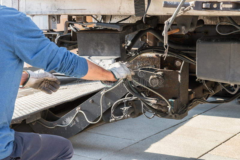 One mechanic is operating a loading ramp of a truck.  stock photo