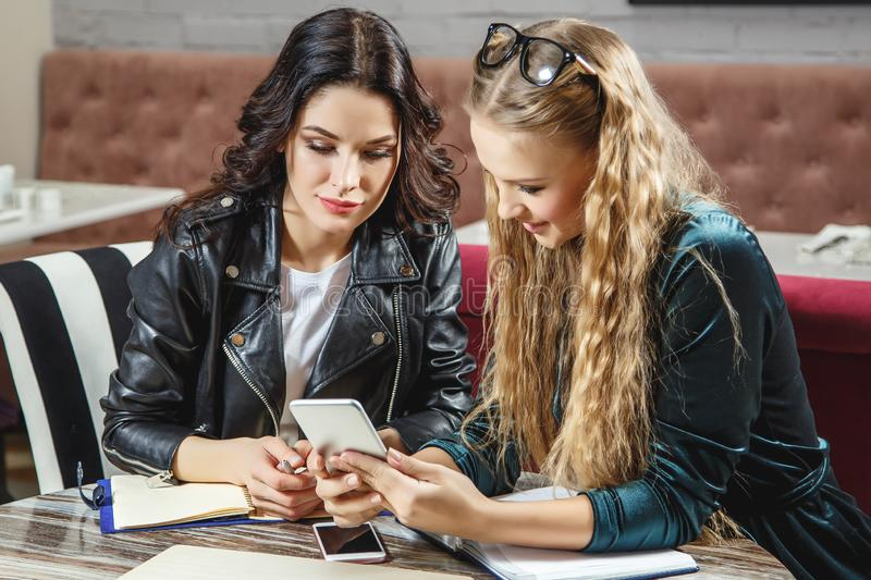 One-on-one meeting. Two young business women sitting at table in cafe. Girl shows colleague information on the smartphone screen. royalty free stock photo