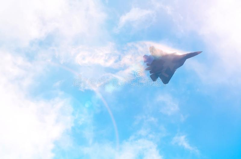 One military fighter aircraft at high speed, flying high clouds in the sky, sunshine glare stock photo