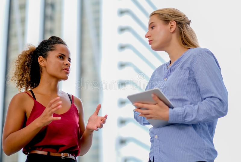 One mixed race girl stand and discuss with white caucasian girl who is holding tablet royalty free stock photos