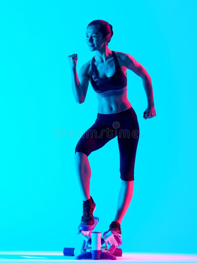 Woman exercsing Stepper fitness exercices isolated. One mixed races woman exercsing Stepper fitness exercices isolated on blue blackground stock image