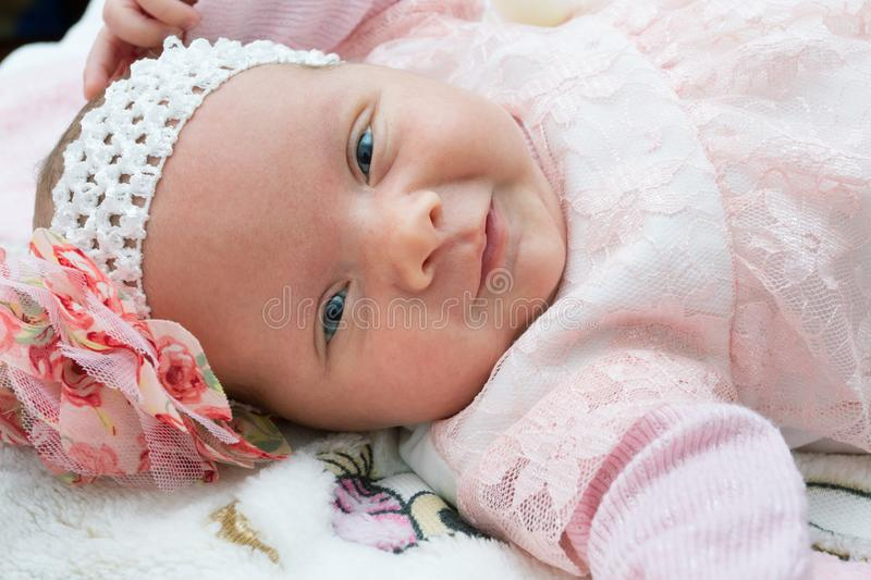 Beautiful newborn baby girl with a flower on her head smiling and looking at camera royalty free stock images