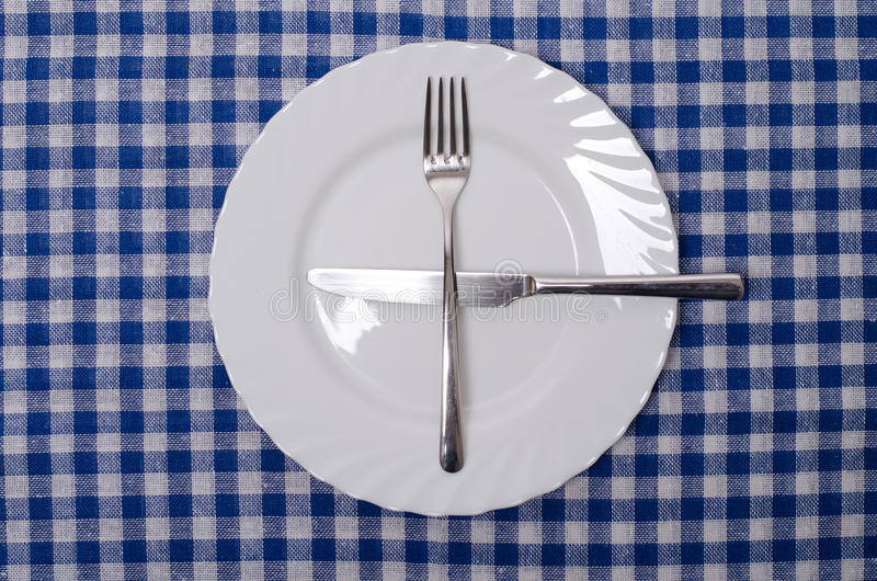One more please - table manners. Isolated on blue tablecloth stock photos