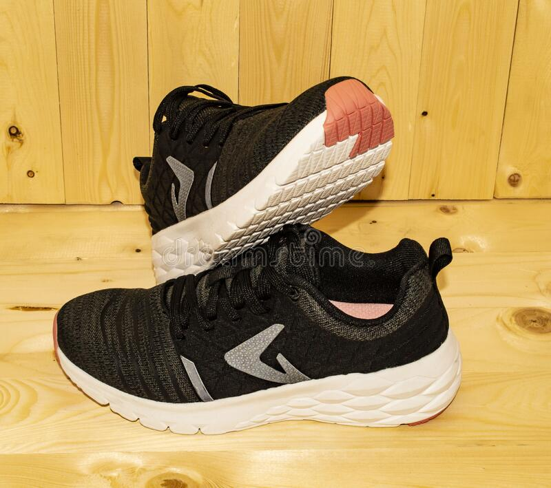 One more view of black white pink colours of Sneakers are shoes primarily designed for sports or other forms of physical exercise. Wooden background for black royalty free stock photos