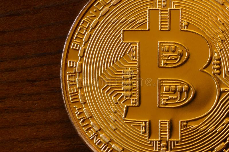 One new golden physical bitcoin is lies on dark wooden backgound, close up. High resolution photo. Cryptocurrency mining concep stock photography