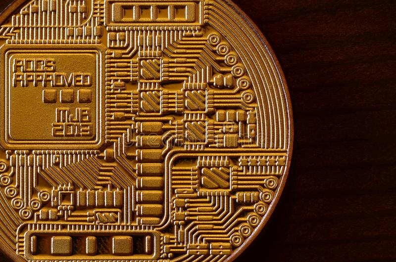 One new golden physical bitcoin is lies on dark wooden backgound, close up. High resolution photo. Cryptocurrency mining concep stock images