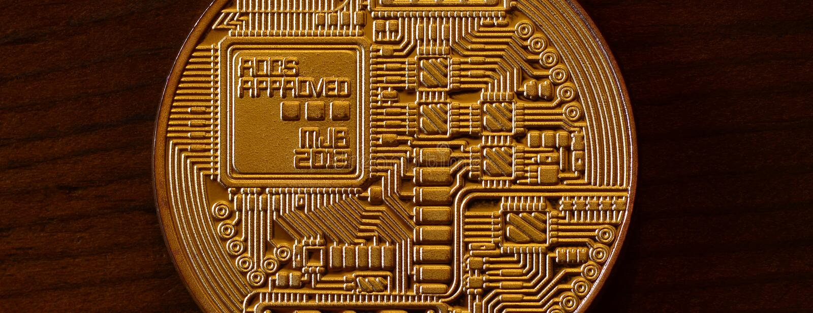One new golden physical bitcoin is lies on dark wooden backgound, close up. High resolution photo. Cryptocurrency mining concep royalty free stock photos