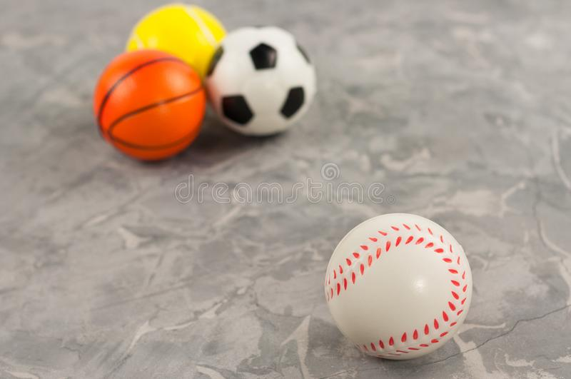 One new rubber soft baseball ball on background of three different sports balls. On old worn cement stock photography