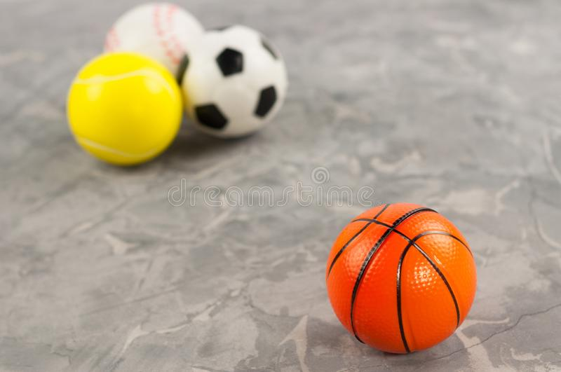 One new rubber soft basketball ball on background of three different sports balls. On old worn cement stock image