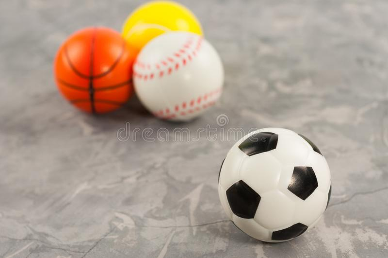 One new rubber soft soccer ball on background of three different sports balls. On old worn cement stock image