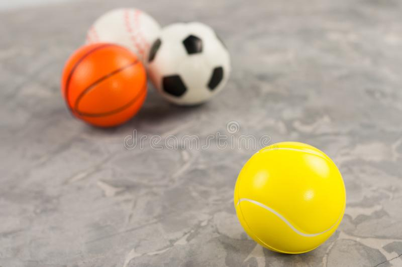 One new rubber soft tennis ball on background of three different sports balls. On old worn cement royalty free stock photography