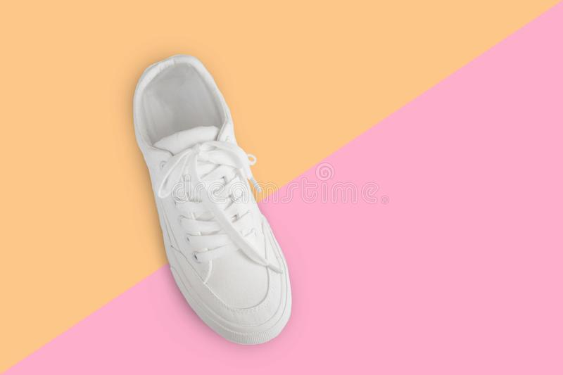 One new white female or teen sneaker isolated on trend yellow-pink background. White textile sneaker with rubber soles with tied stock photography