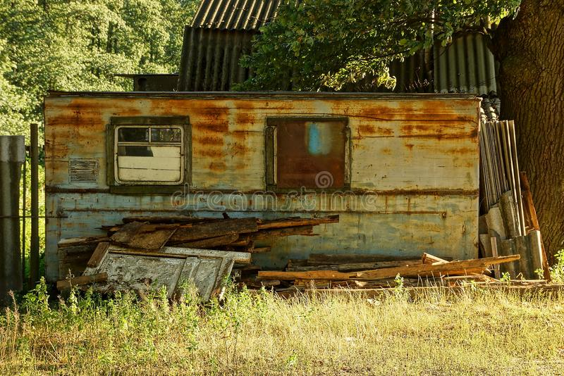 Old rusty trailer with windows in the grass on the street. One old rusty trailer with windows in the grass on the street royalty free stock image