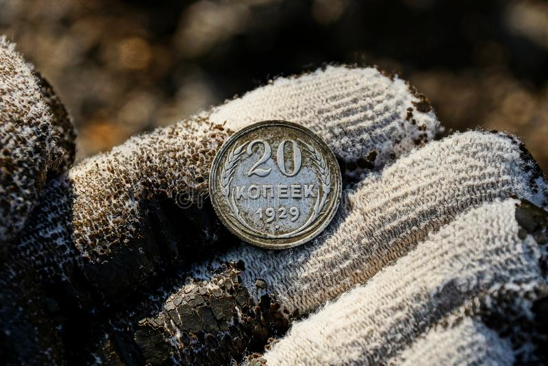 Old silver soviet coin on fingers in glove. One old silver Soviet coin on a gloved hand stock images