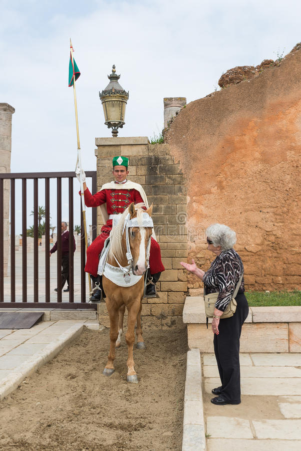 One old tourist woman talk to horse which soldier is sitting. Rabat, Morocco - Mar 20: One old tourist woman talk to horse which one moroccan soldier is sitting stock images