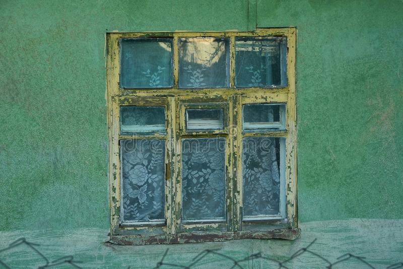 One old yellow wooden window on the green wall stock photo